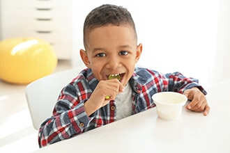 Young boy eating yogurt.