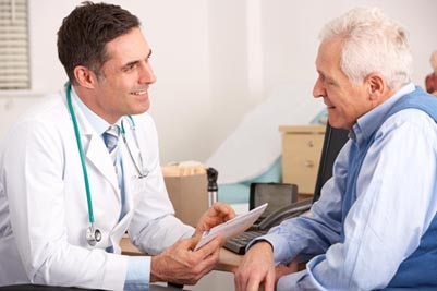 A health care professional talking with a patient in his office.