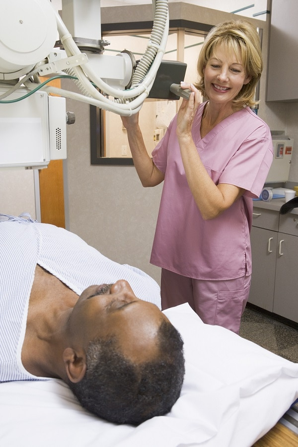 Technician sets up x-ray machine and patient lies on x-ray table.