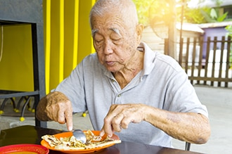 An older man eating a meal.