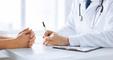Doctor writing data on a clipboard while sitting in front of a patient with folded hands.