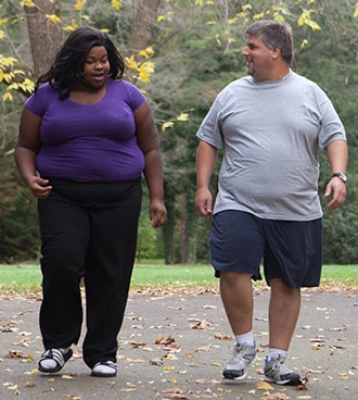 An overweight woman and man taking a walk.