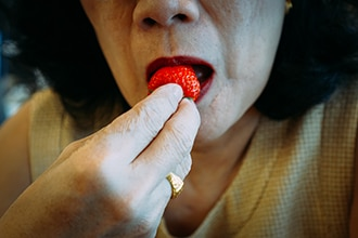Photo of woman eating a strawberry.
