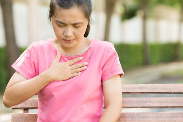 A woman experiencing heartburn and pressing a hand to her chest.