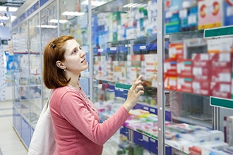 A woman shops for an over-the-counter medicine at a pharmacy.