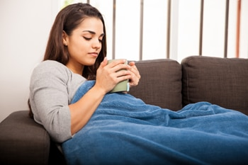 Young woman sitting on a sofa wrapped in a blanket and holding a large mug.