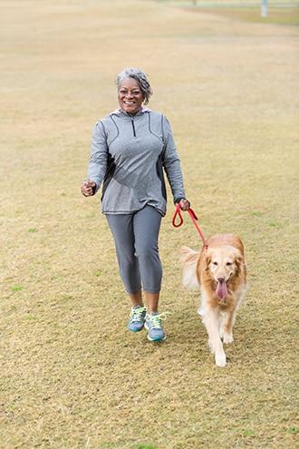 Woman walking a dog outdoors