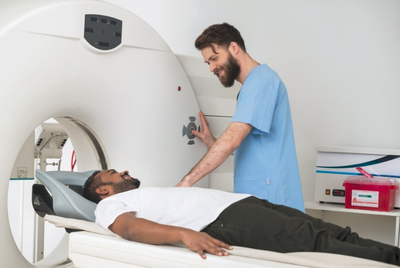 A man lying on a table ready to slide into a doughnut-shaped CT machine with a health care professional by his side.