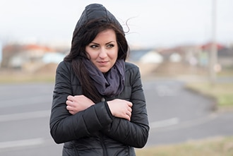 Woman with a coat shivering outdoors