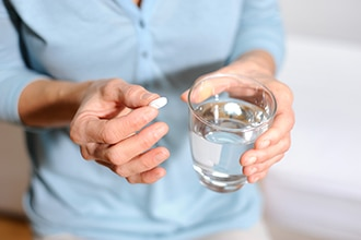 A woman holding a capsule and a glass of water