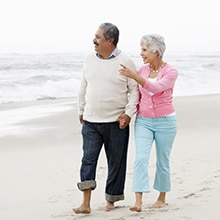 a senior couple walking on the beach
