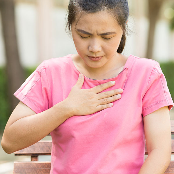 Woman has acid reflux on a park bench