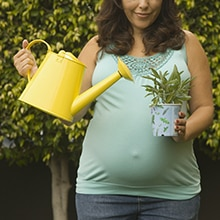 pregnant woman with a watering can