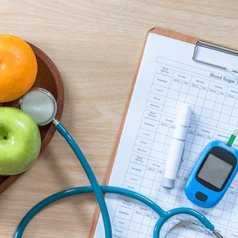 Diabetes monitor, fruit, and clipboard