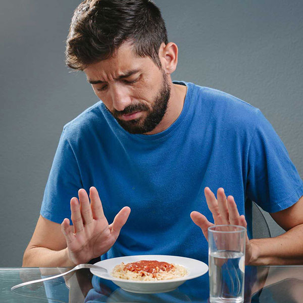 man with no appetite in front of a meal