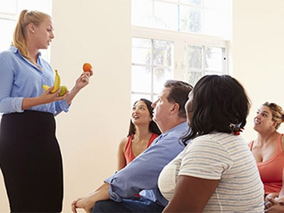 A health educator holding fruit and speaking to a group about lifestyle changes
