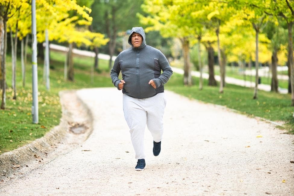 Overweight man jogging in the park.