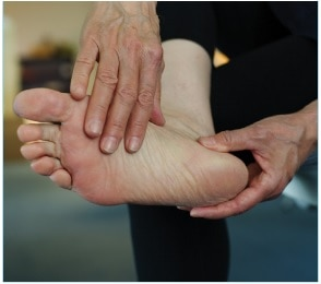 A person examines the sole of the foot.