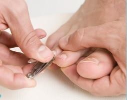 A person cuts their toenails.