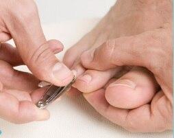 Una persona se corta las uñas de los pies.