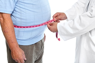 A health professional measures a man's waist.