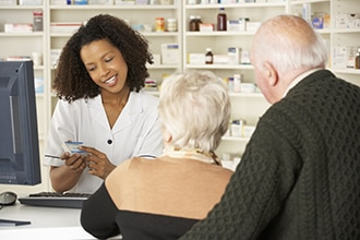 A couple talking to a pharmacist.