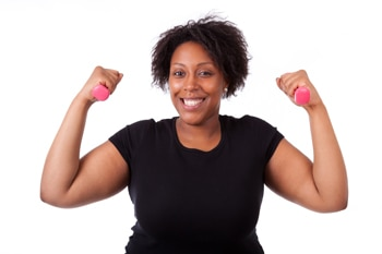 Una mujer que sonríe y levanta unas pesas de mano.
