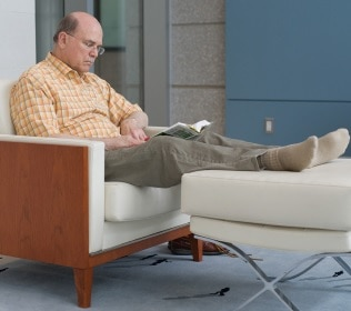A seated man reads a book and rests his feet on a small foot chair.
