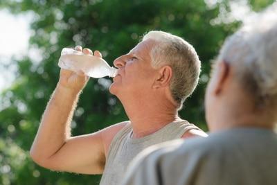 De un hombre en ropa de ejercicio al aire libre que bebe de una botella de agua.