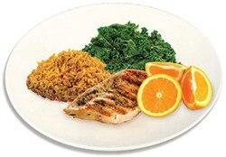 Plato de comida que consiste de pollo, naranja, arroz, y espinaca