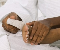 A woman files the sole of her foot with a pumice stone.