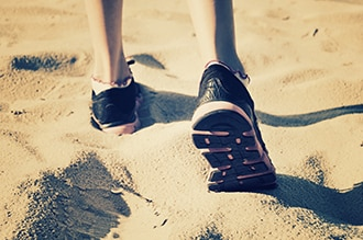 A person in sports shoes walks in the sand.