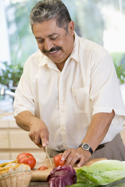 An older male slices up vegetables as he prepares a meal.