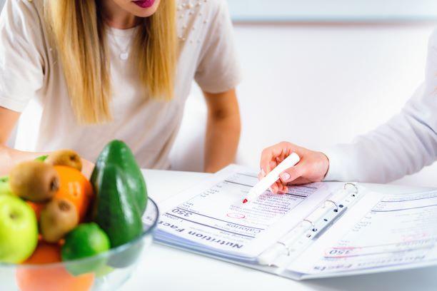 Una paciente se sienta a la par de una mesa y revisa un cuadro dietético con un profesional de la salud.