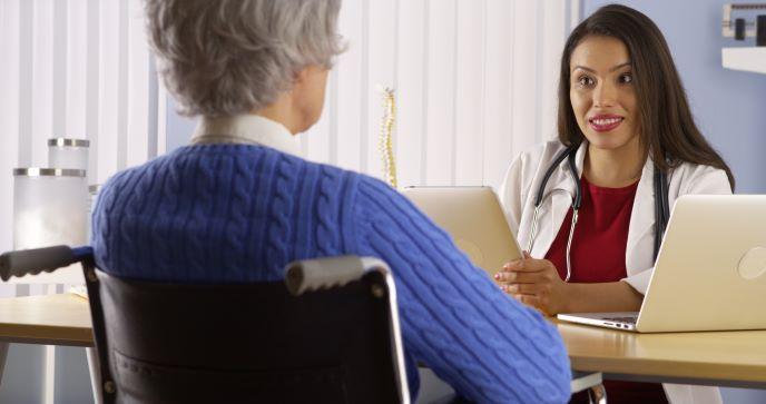 Una profesional de la salud sentada detrás de su escritorio habla con una paciente sentada frente a ella en una silla de ruedas.