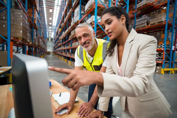Male and female coworkers look at a computer screen while in a warehouse.