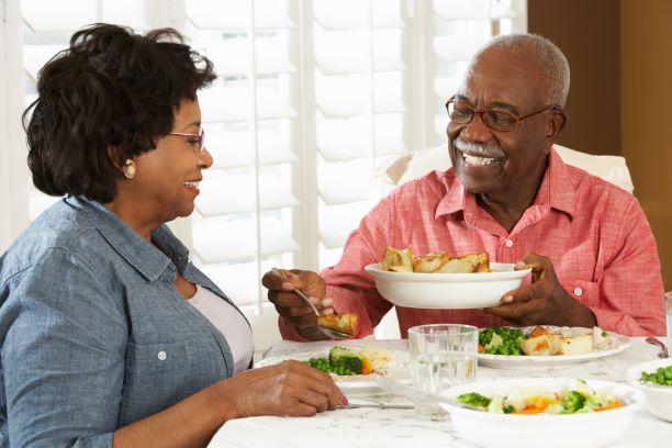 Un hombre mayor le sirve comida de un recipiente a una mujer sentada a su lado en una mesa de comedor.