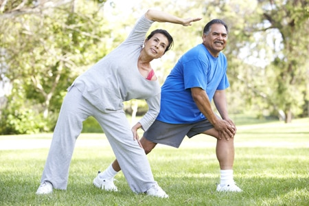 Older man and woman in exercise clothes stretching in a park.
