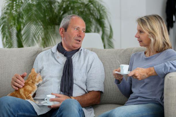 Un hombre mayor habla con su compañera mientras están sentados juntos en un sofá.