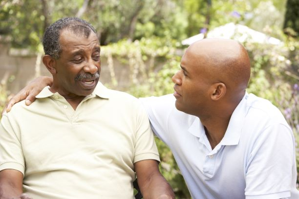 Un hombre mayor está sentado mientras habla con un hombre más joven que descansa su brazo sobre el hombro del hombre mayor.