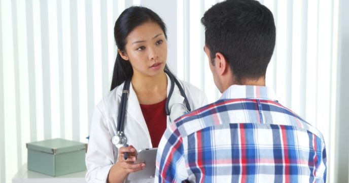 A health care professional talks with a patient.
