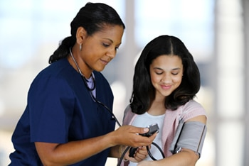 A health care professional checking a patient's blood pressure.