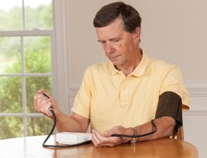 A photo of an older man checking his blood pressure at home.