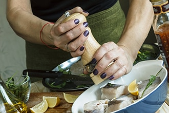 Woman grinding pepper on fresh fish with lemon and herbs.