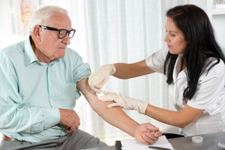 A photo of a nurse drawing blood from an older man at a doctor's office.