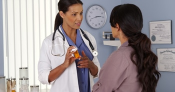 A health care professional talking to a patient about medicine.