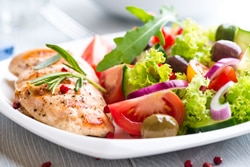 Photo of a healthy food choice: a grilled chicken breast with salad.