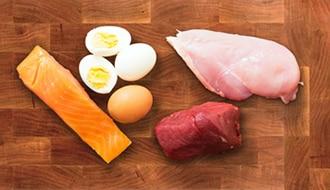Un pedazo  de salmón, huevos, un filete de pollo y un pedazo de carne roja.