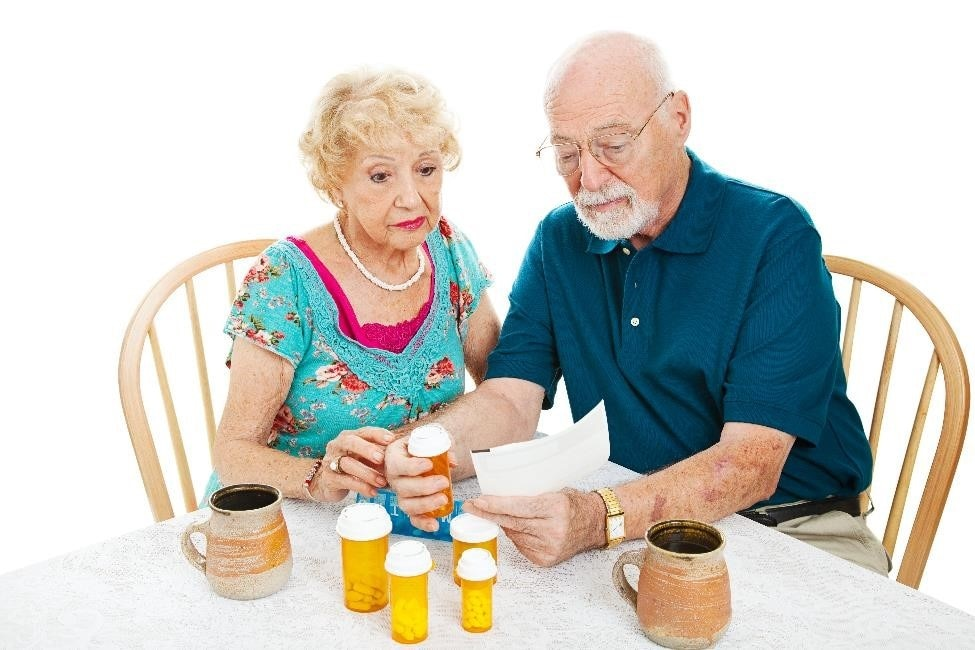 Older adult couple sitting at a table, looking at medicine bottles and receipts.
