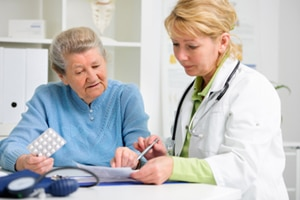 A photo of a health care provider talking about medicine to an older patient.
